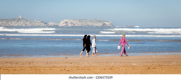 Morocco Dec. 22, 2012- A group of four young local women wearing Muslim headscarves walk barefoot on the beach in the coastal town of Essaouira. The picturesque fishing village attracts many tourists.