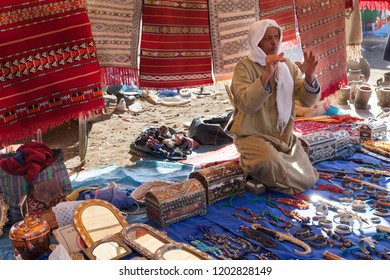 Morocco - Dec. 27, 2012: Outdoor souk market. Merchant selling rugs and jewelry interacts with shoppers.