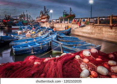 Morocco Essaouira harbor at night. Selective focus on the foreground red fish netting and floats. Background motion blur of colorful blue boats and seagulls in flight. Picturesque seaside village.
