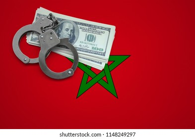 Morocco flag  with handcuffs and a bundle of dollars. The concept of breaking the law and thieves crimes