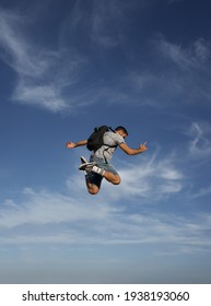 Morocco - January 20, 2021; Adventurous man jumping very high in the blue sky out of excitement and joy