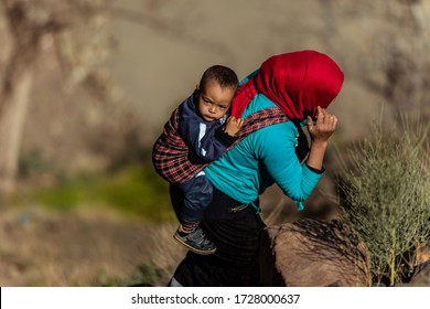 Morocco - March 12, 2019. A Berber woman with a child on her back, tied with a scarf, walks along the slope of the mountains to her settlement. Traditional Berber adobe architecture.