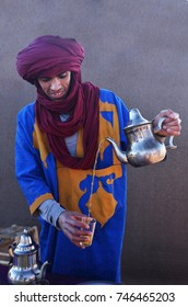 MOROCCO - MARCH 2017: Berber man pouring tea from a traditional metal kettle into glasses in the Berber camp in Sahara desert on March 23, 2017 in Morocco