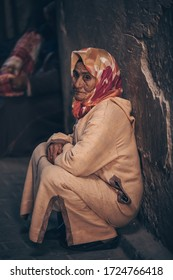 Morocco. Marrakesh. Medina. March 11, 2019.  - A Moroccan elderly woman sits leaning back against a wall in the old city.