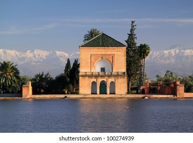 Morocco Marrakesh  Menara Pavilion and  Gardens reflected on the lake in late afternoon sunshine with snow covered peaks of the Atlas Mountains in the background