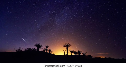 Morocco Sahara desert starry night sky over the oasis. Traveling to Morocco. Glow over the palm trees of the oasis. Billions of stars in the night sky, milky way. Panoramic photo