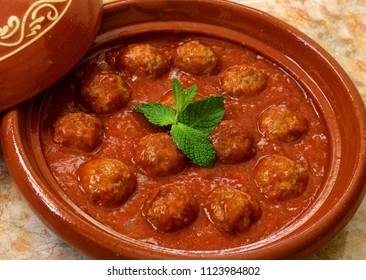 Morocco. Tajine of Kafta - Typical Moroccan and Lebanese dish of meatballs in a tomato sauce with paprika, cumin, onions and garlic - cooked in a clay 'tajine' dish.