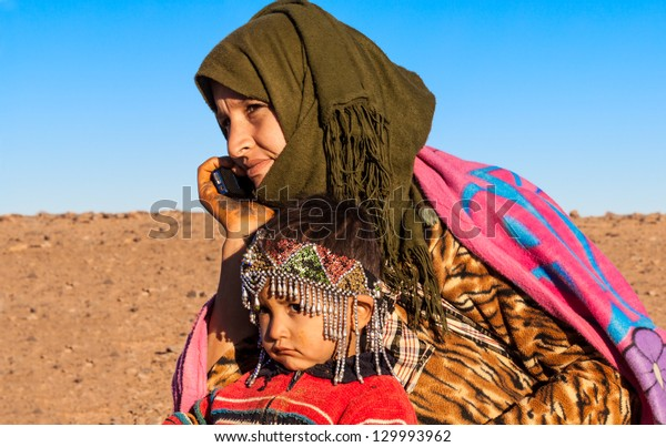 MOROCCO-DEC 28: An unidentified nomad mother on a cell phone in the Sahara desert  on Dec. 28, 2012 in Morocco. The telecom regulator ANRT reports mobile penetration in Morocco at more than 110%.