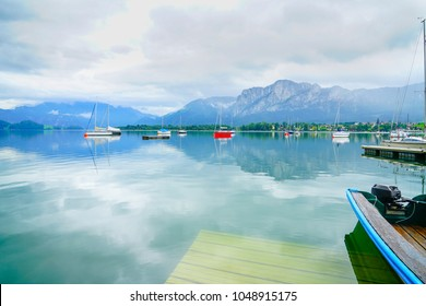Morred boats float lazily on calm natural and beautiful alpine Lake Mondsee surrounded by Austrian Alps.