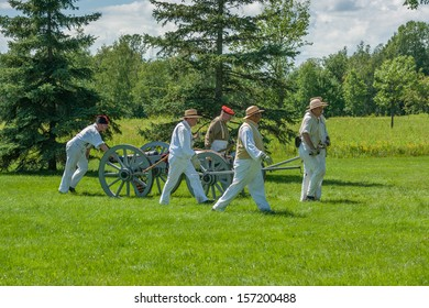 MORRISBURG, CANADA - JULY 14: Men pulling a cart and canon during the Battle of Crysler's Farm reenactment on July 14, 2013 near Morrisburg, Ontario.