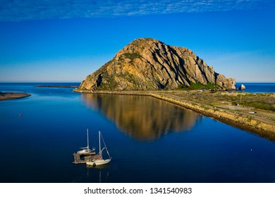 Morro Bay rock at the Central California coast with reflections in the water.