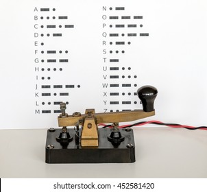 Morse Code Key with wall display of Morse Code