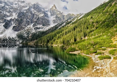 morskie oko lake view with green forest and snow peak mountains of tatry, poland