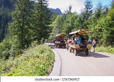 Morskie oko, Poland - August 08, 2019: Group of tourists on the horse cart on the road to Morskie Oko lake Tatra Mountains