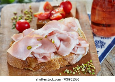Mortadella with pistachio on fresh bread slice, with cherry tomatoes and rose sparkling wine.