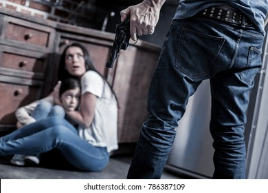 Mortal danger. Selective focus of an angry man holding his handgun while putting his family into the mortal danger