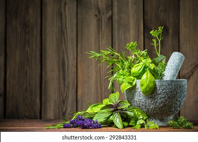 Mortar with aromatic kitchen herbs on wooden table