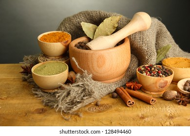 mortar, bowls and spoons with spices, on table on grey background