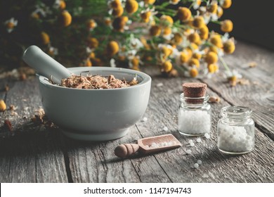 Mortar of dried healing herbs, homeopathic globules and bunch of chamomile plants. Homeopathy and herbal medicine.