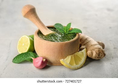 Mortar with pestle and chutney mint sauce on table