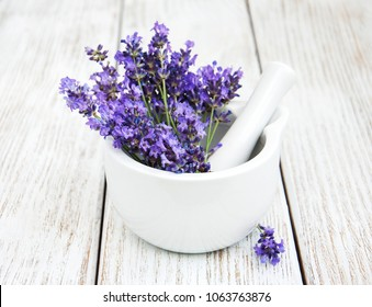 mortar and pestle with  fresh lavender on a old wooden background