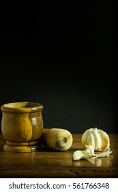 Mortar and Pestle with garlic on a wooden table