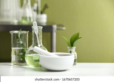 Mortar with pestle and natural ingredients on white table in cosmetic laboratory