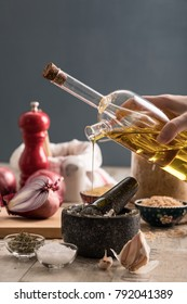 Mortar and pestle, olive oil, red onion, orzo, garlic on wooden rustic background
