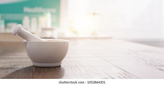 Mortar and pestle on the pharmacist's table and pharmaceutical products on the background