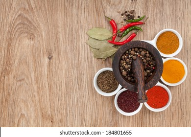 Mortar and pestle with pepper and spices on wooden table