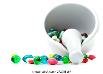 Mortar and pestle with pills against a white background