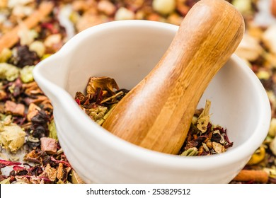 Mortar and pestle set with herbal tea on white wooden background