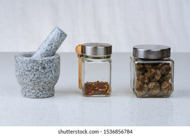 Mortar and pestle with two apothecary jars of herbal and green teas lined up on a white background.