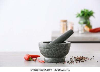 Mortar with spices and pestle on light table in kitchen