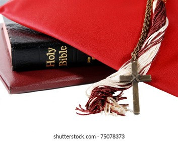 mortarboard with tassel, diploma, bible and cross - for a religious graduation theme, isolated on white
