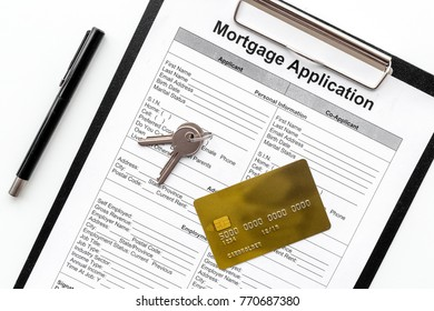 Mortgage application near bank card and apartment keys on white background top view