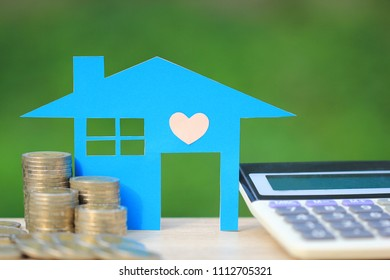 Mortgage calculator, Blue house model and stack of coins money on natural green background,Interest rates and Banking concept