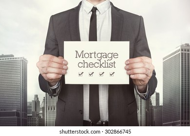 Mortgage checklist  on paper what businessman is holding on cityscape background