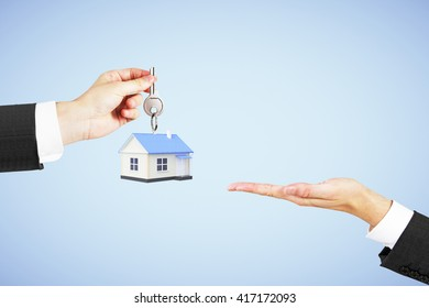 Mortgage concept with businessman handing house with key to another man on blue background