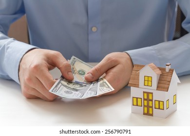 Mortgage concept. Close-up view of businessman holding fan of one hundred dollar bills in hands and sitting at the white wooden table with small toy house