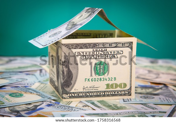 Mortgage concept. House made of dollars banknotes on a green background and a heap of money. Close-up