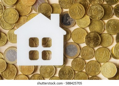Mortgage concept with toy house and Euro coins
