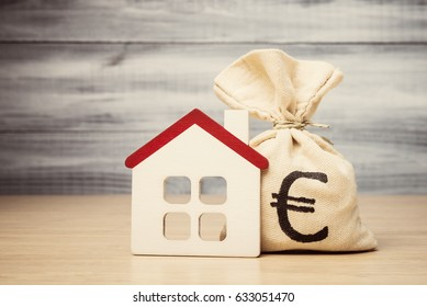 Mortgage concept with toy house and money bag with Euro symbol