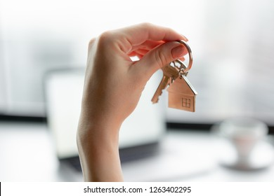 Mortgage concept. Woman in red coral business suit holding key with house shaped keychain. Modern light lobby interior. Real estate, hypothec, moving home or renting property.