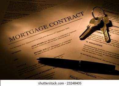 Mortgage contract for sale of real estate property with a pen and house keys