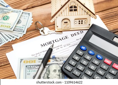 Mortgage deed with calculator, money, model of house and key on the wooden background. Real estate concept.