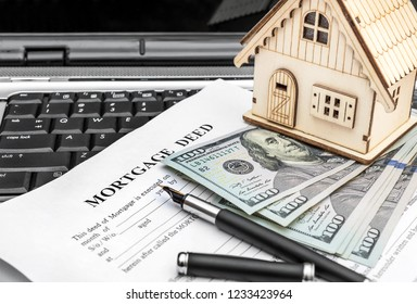 Mortgage deed with model of house on laptop keyboard.