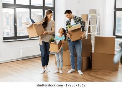 Hypotheken-, Familien- und Immobilienkonzept - glückliche Mutter, Vater und kleine Tochter mit Sachen in Kisten, die in ein neues Zuhause umziehen