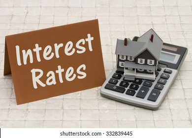 Mortgage Interest Rates, A gray house, brown card and calculator on stone background with text Interest Rates