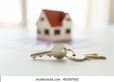mortgage, investment, real estate and property concept - close up of home model, money and house keys